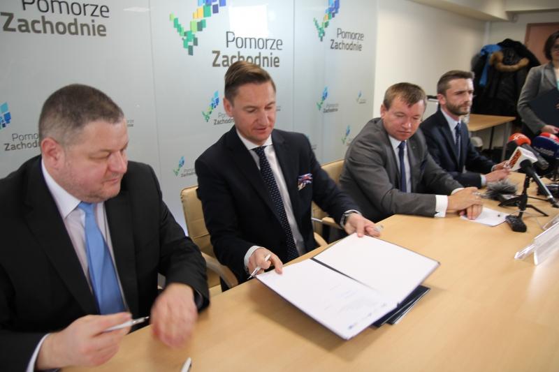 Marszałek Olgierd Geblewicz przekazuje dokument do podpisu Przemysławowi Cieszyńskiemu, członkowi Zarządu BGK. (fot. wzp.pl)