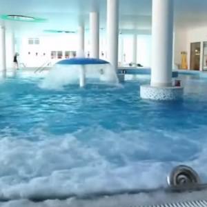 Baseny w hotelu Grand Lubicz w Ustce (pomorskie)    Rekreacyjny basen ze zjeżdżalnią, sztuczną rzeką oraz podwodnymi leżankami wodno-powietrznymi o łącznej powierzchni 474 mkw. to doskonała alternatywa dla pochmurnych dni na plaży – zapewnia Grand Lubicz w Ustce. Ale hotel oferuje też basen sportowy o powierzchni 250 mkw. oraz basen zewnętrzny z wodą solankową o właściwościach leczniczych (364 mkw.). Na klientów czekają też wanny z hydromasażem, sauna fińska czy łaźnia parowa. Dla dzieci przewidziano brodzik z atrakcjami wodnymi.   Godzina w hotelowym aquaparku kosztuje od osoby 16 zł/18 zł od poniedziałku do piątku (w zależności czy przyjdziemy przed, czy po godz. 16). Bilety ulgowe kosztują kolejno: 14 zł/16 zł. Z kolei w weekendy i święta osoby dorosłe płacą 20 zł/22 zł, a osoby do 12 lat i seniorzy – 17 zł/19 zł. Tańsze są za to bilety rodzinne, czyli dla dwóch osób z minimum jednym dzieckiem. Ich ceny wynoszą od 14 do 17 zł. Sauny w każdej z opcji są dodatkowo płatne – 0,55 zł za minutę.    Fot. YouTube