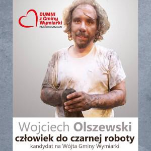 """Wyznaczonym przez Adama Nowaka tropem podążył ubiegający się o stanowisko wójta gminy Wymiarki (woj. lubuskie) Wojciech Olszewski. W odstawkę poszedł krawat i garnitur. Na plakacie Olszewski prezentuje się umorusany, w brudnym t-shircie, ze szmatą w dłoni i hasłem """"człowiek do czarnej roboty""""."""