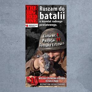 """Na wojskowy styl postawił też Tomasz Ertman, walczący o mandat radnego powiatowego w Sochaczewie. Ubrany w mundur i wojskowy hełm mierzy do spoglądających w jego stronę z karabinu. Całość zwieńcza hasło """"The Red Big One""""."""