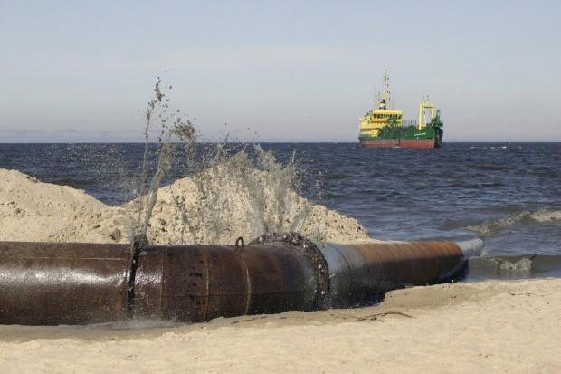 Refulacja polega na dostarczaniu rurociągami na plażę mieszanki piasku i wody, a następnie rozgarnianiu i profilowaniu przez maszyny budowlane pozostałego na plaży piasku (fot. Urząd Morski w Gdyni)