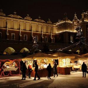 """Kraków    Targi Bożonarodzeniowe w Krakowie wiążą się z ponad stuletnią tradycją i sięgają czasów, kiedy były jeszcze nazywane """"Jarmarkami"""".   W tym roku to świąteczne wydarzenie rozpoczęło się 29 listopada na Krakowskim Rynku Głównym. Dzień później 30 listopada zaplanowano wielką inaugurację świątecznej iluminacji.   Kupcy co roku oferują szeroką gamę świątecznych produktów, takich jak bańki ręcznie malowane, ozdoby choinkowe, artykuły dekoracyjne, stroiki świąteczne, wyroby ceramiczne, wyroby z drewna, wełny, sukna, szkło artystyczne, biżuteria, pamiątki, pocztówki, kalendarze. Można skosztować wyśmienitych potraw z grilla, tradycyjnego oscypka prażonego na grillu z żurawiną oraz napić się grzańca galicyjskiego. Na miłośników małego co nieco czekać będą też prażone orzechy, pieczone kasztany oraz świąteczne ciasteczka i pierniki.   Targom Bożonarodzeniowym towarzyszą liczne imprezy: Korowód Kolędniczy, Obrzęd Dziadów Polskich - inspirowanych dramatem Mickiewicza, prezentacje Gmin Małopolski, spotkania opłatkowe z dostojnikami miasta itp. W ramach targów przy pomniku Adama Mickiewicza spotkają się twórcy szopek.   Tegoroczne świąteczne targi w Krakowie potrwają do 26 grudnia.   fot.krakow.pl"""